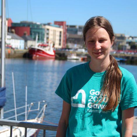 Tina steht an einem Hafen mit Booten, Meer und blauem Himel im Hintergrund