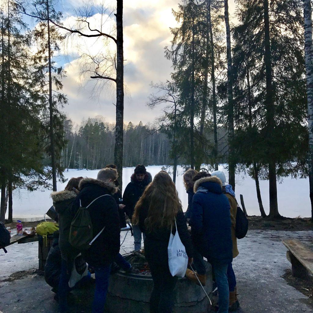 Viele Menschen um ein Lagerfeuer herum mit Essen