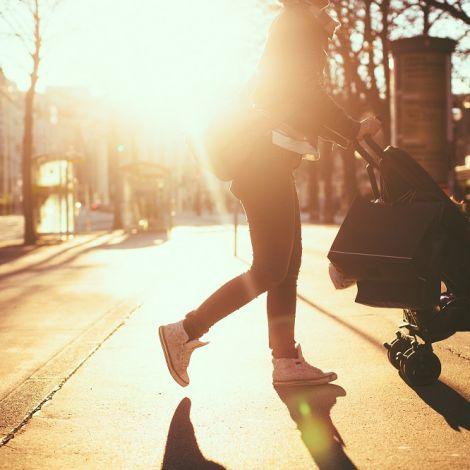 Mutter schiebt einen Kinderwagen bei Sonnenuntergang