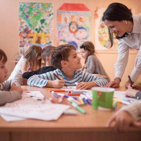Schüler basteln unter Aufsicht des Lehrers