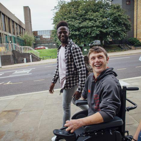 Student im Rollstuhl unterhält sich mit anderen Studierenden