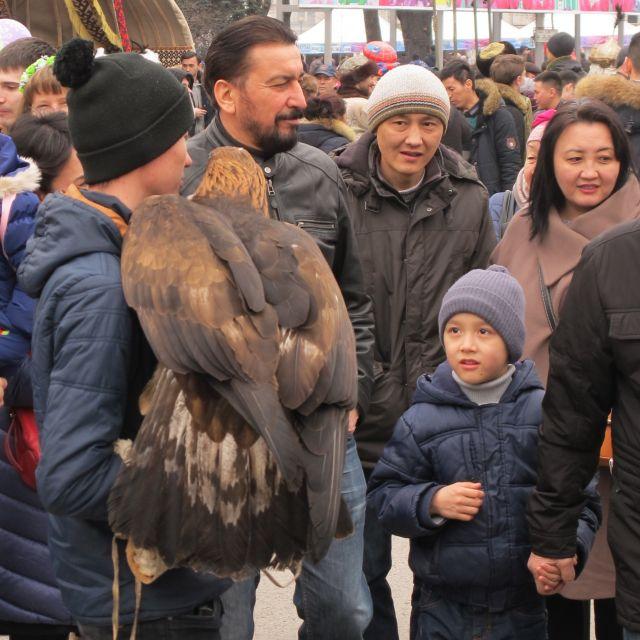 Ein Mann und einem Greifvogel auf dem Arm, in einer Menschenmenge stehend.