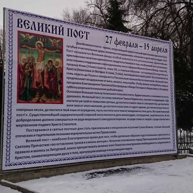 """Poster an einem Zaun mit der Überschrift """"Große Fastenzeit"""" 27. Februar bis 15. April, einer Ikone des gekreuzigten Christus und viel Text zur Erläuterung der Fastentradition in russischer Sprache"""
