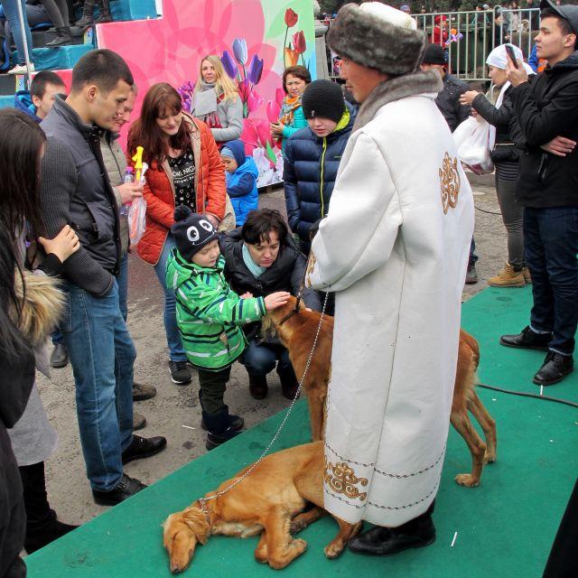Man in kasachischer Tracht mit zwei Jagdhunden, die von Kindern gestreichelt werden.