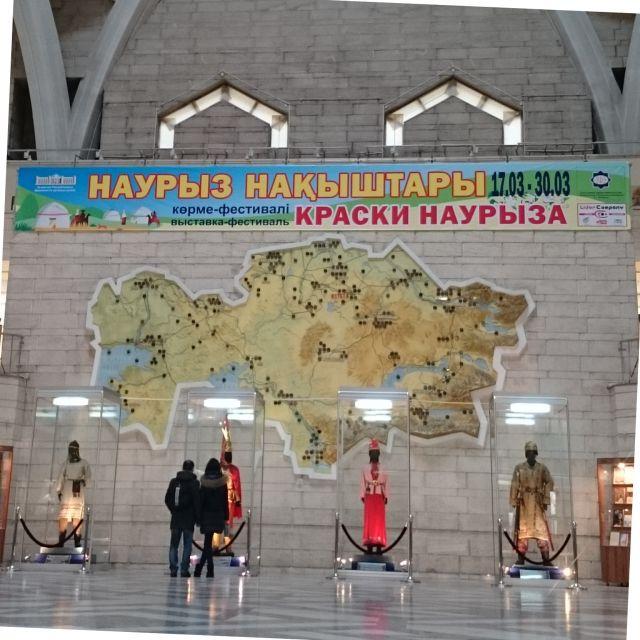 Eingangshalle des kasachischen Nationalmuseums mit einer Karte von Kasachstan, Trachten und einem Nauryz-Poster