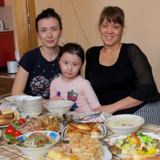 Zwei Frauen und ein Kind sitzen an einem gedeckten Tisch