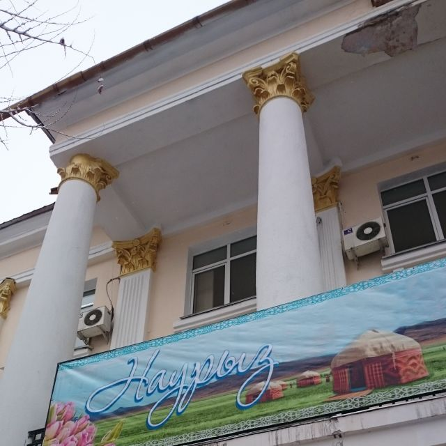 Nauryz-Poster an einer Hausfassade mit griechisch anmutenden Säulen