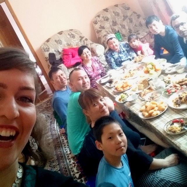 Selfie mit Theresa im Vordergrund und einer kasachischen Familie an einem gedeckten Tisch im Hintergrund.