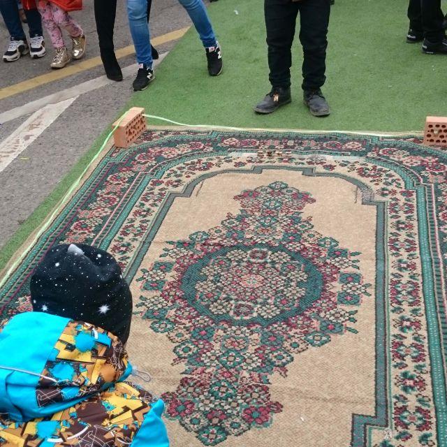 Ein Teppich der mit Stricken umgrenzt ist, im Vordergrund ein Junge, der etwas wirft.