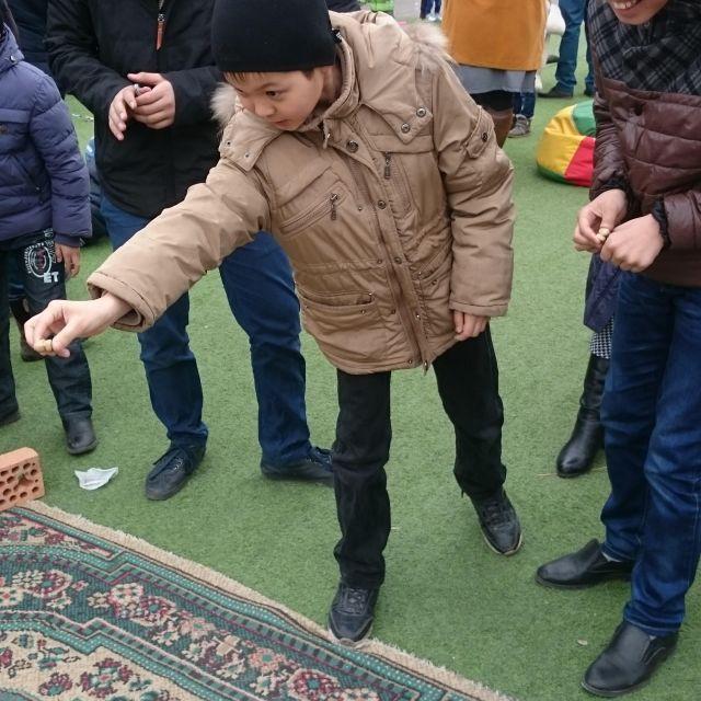 Ein Junge, an der Kante eines Teppichs, der etwas wirft und konzentriert zielt.