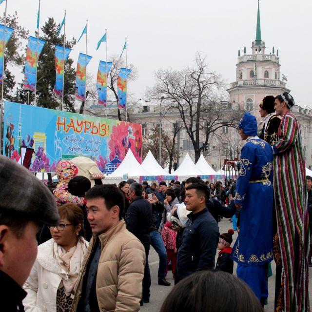 Drei Männer auf Stelzen in bunten Kostümen in einer Menschenmenge
