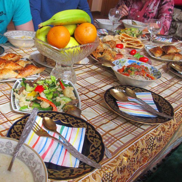Festlich gedeckter Tisch mit Tellern mit kasachischen Ornamenten, kasachischen Salaten und Obst.