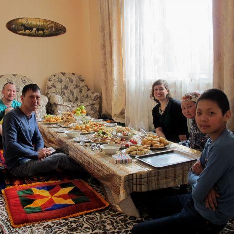 Langer, reich gedeckter, niedriger Tisch an dem auf dem Boden sitzend verschiedene Menschen sitzen und in die Kamera lächeln.