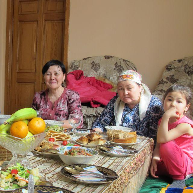Zwei ältere Frauen und ein Kind sitzen an einem gedeckten Tisch