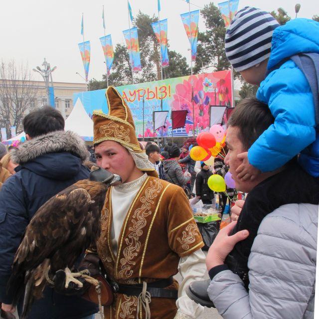 Ein Mann mit kasachischer Tracht und einem Greifvogel auf dem Arm, in einer Menschenmenge stehend.