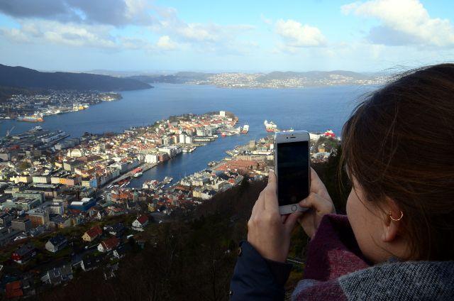 Frau fotografiert Bergen von einem Berg außerhalb der Stadt mit einem Smartphone