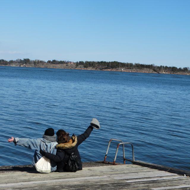 Zwei Mädchen sitzen auf dem Steg am Wasser