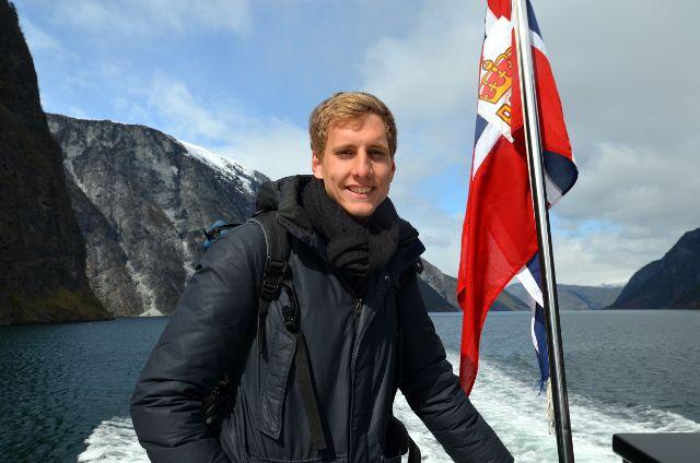 Student Henning auf Boot im Fjord, neben im Norwegenfahne, im Hintergrund Berge