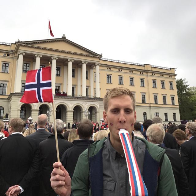 Junger Mann mit rot-weiß-blauer Norwegen-Flagge vor dem Schloss in Oslo