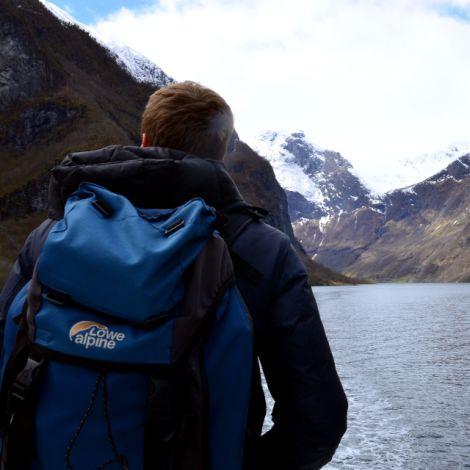 Mann steht auf Boot, im Hintergrund hohe verschneite Berge