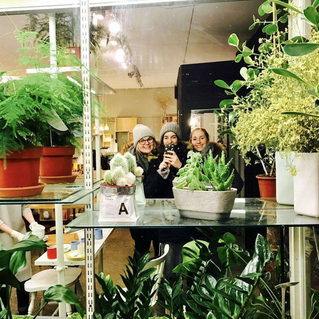 Spiegelfoto von drei Mädchen in einem Café mit vielen Pflanzen