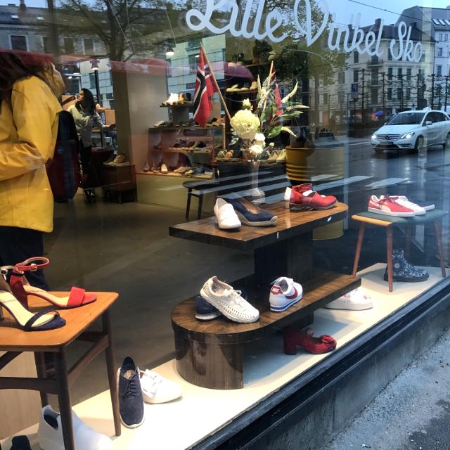 Schaufenster eines Schuhgeschäftes, in dem nur noch rote, blaue und weiße Schuhe stehen