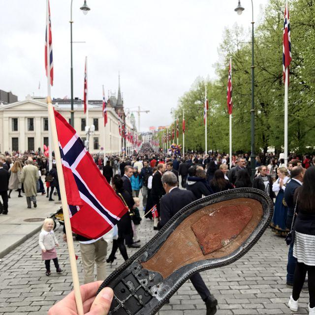 Hand hält schwarze Schuhsohle in die Höhe, im Hintergrund Boulevard mit Norwegen-Beflaggung