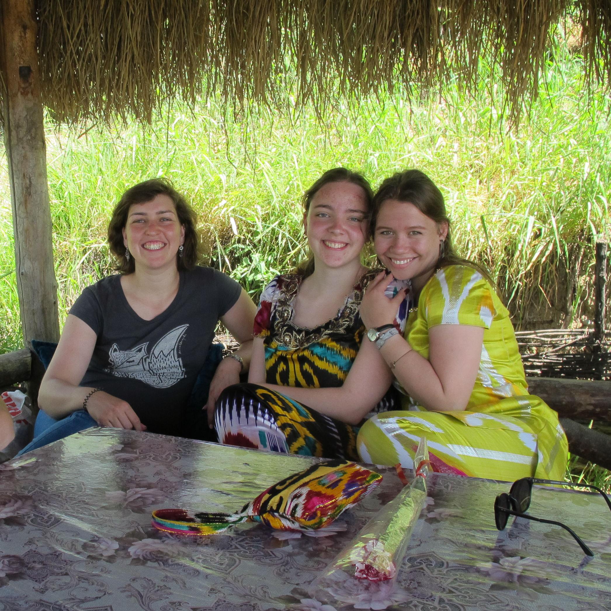 Drei Frauen auf einer Terasse, zwei davon in Atlasgewändern, eine in westlicher Kleidung.
