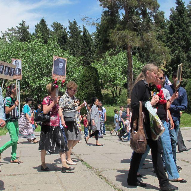 Menschen mit Plakaten mit schwarz-weißen Fotos laufen durch den Siegespark in Duschanbe.