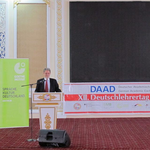 Der Deutsche Botschafter auf einem Podium neben Werbetafeln des DAAD und des Goethe-Instituts