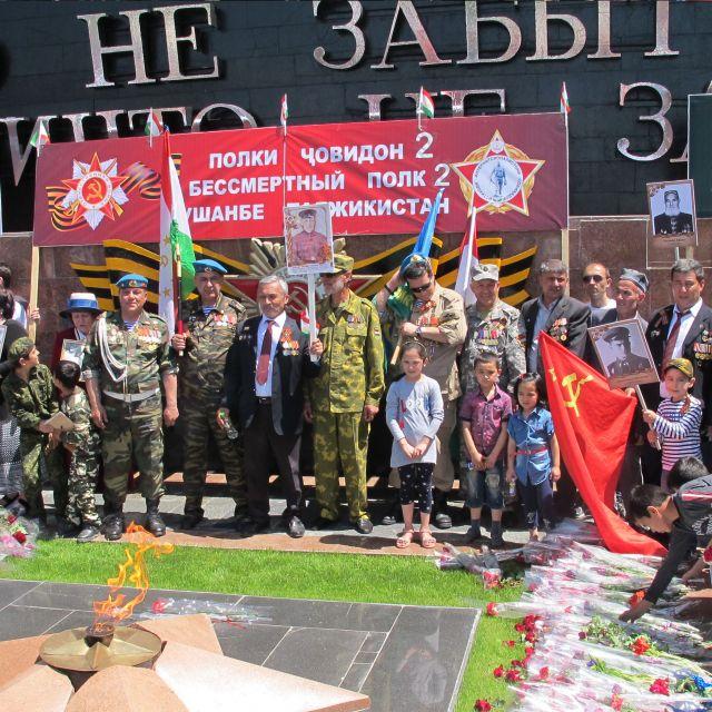 Uniformierte und nichtuniformierte Menschen stehen vor dem ewigen Feuer im Siegespark in Duschanbe, Tadschikistan.