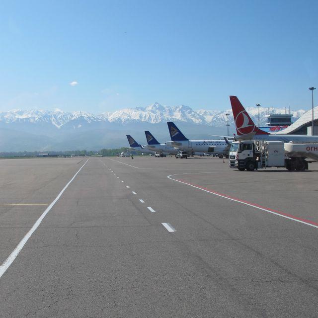 Die Startbahn mit den wartenden Flugzeugen und einem Ausblick auf das Tien Shan Gebirge