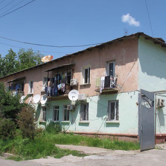 Ein wohnblock mit Satelitenschüsseln an einer Straße in Duschanbe.