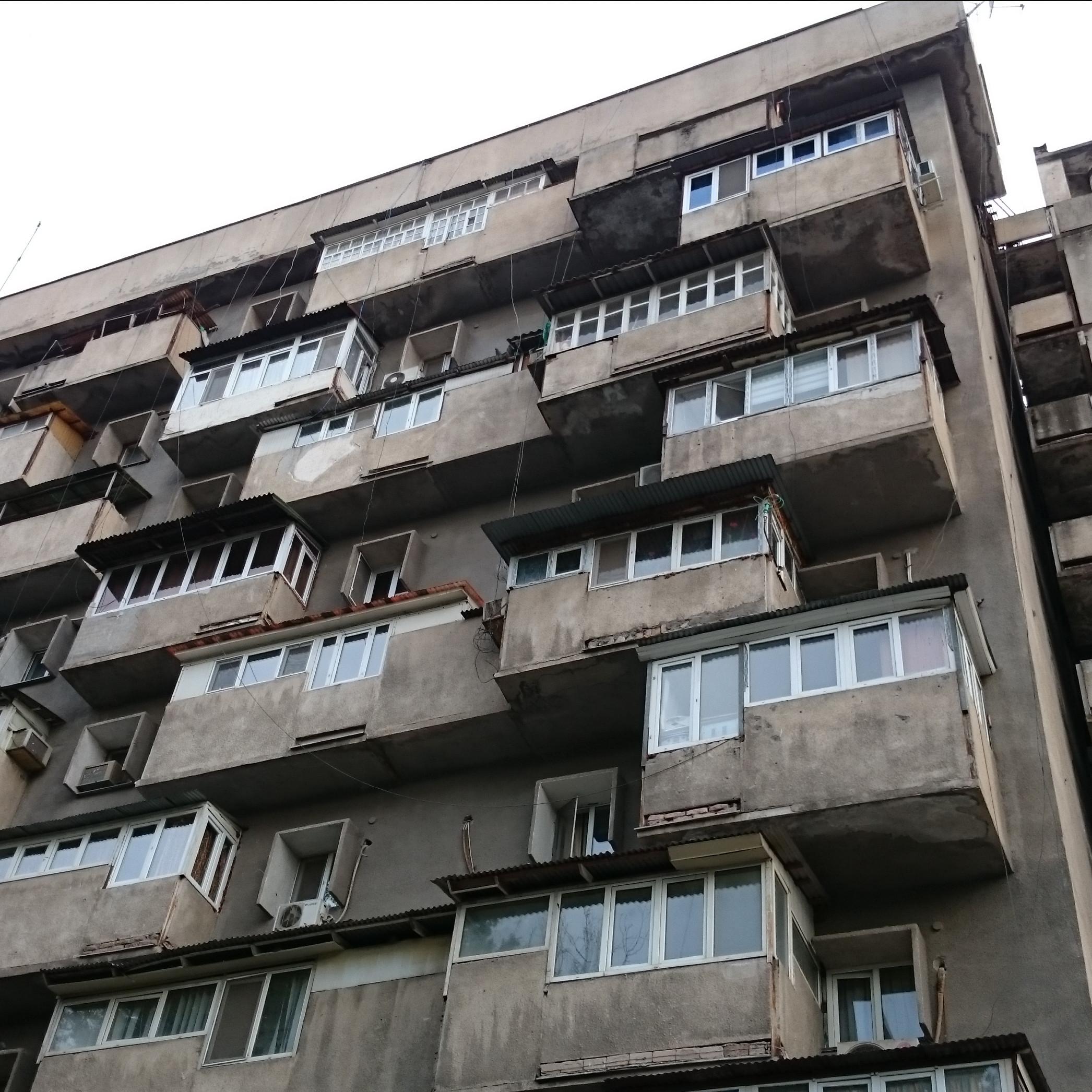 Grauer Wohnblock von unten fotografiert mit vielen Wohnungen.