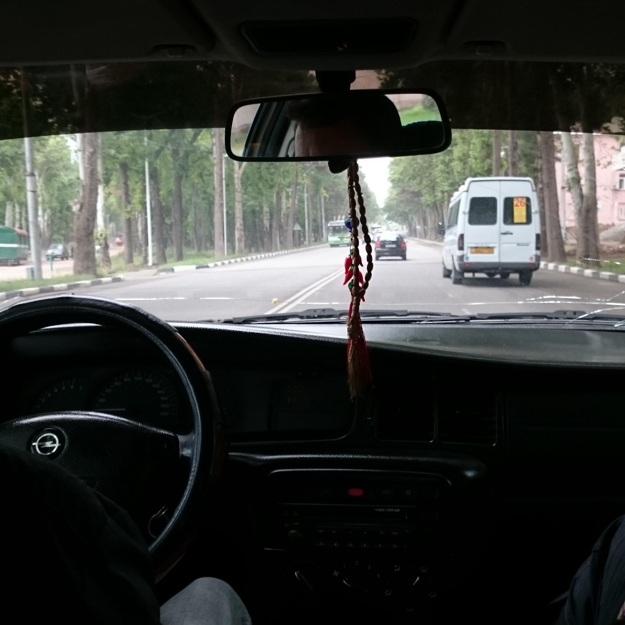 Blick aus einem alten Opel auf eine Straße in Duschanbe, wo eine Marschrutka fährt.