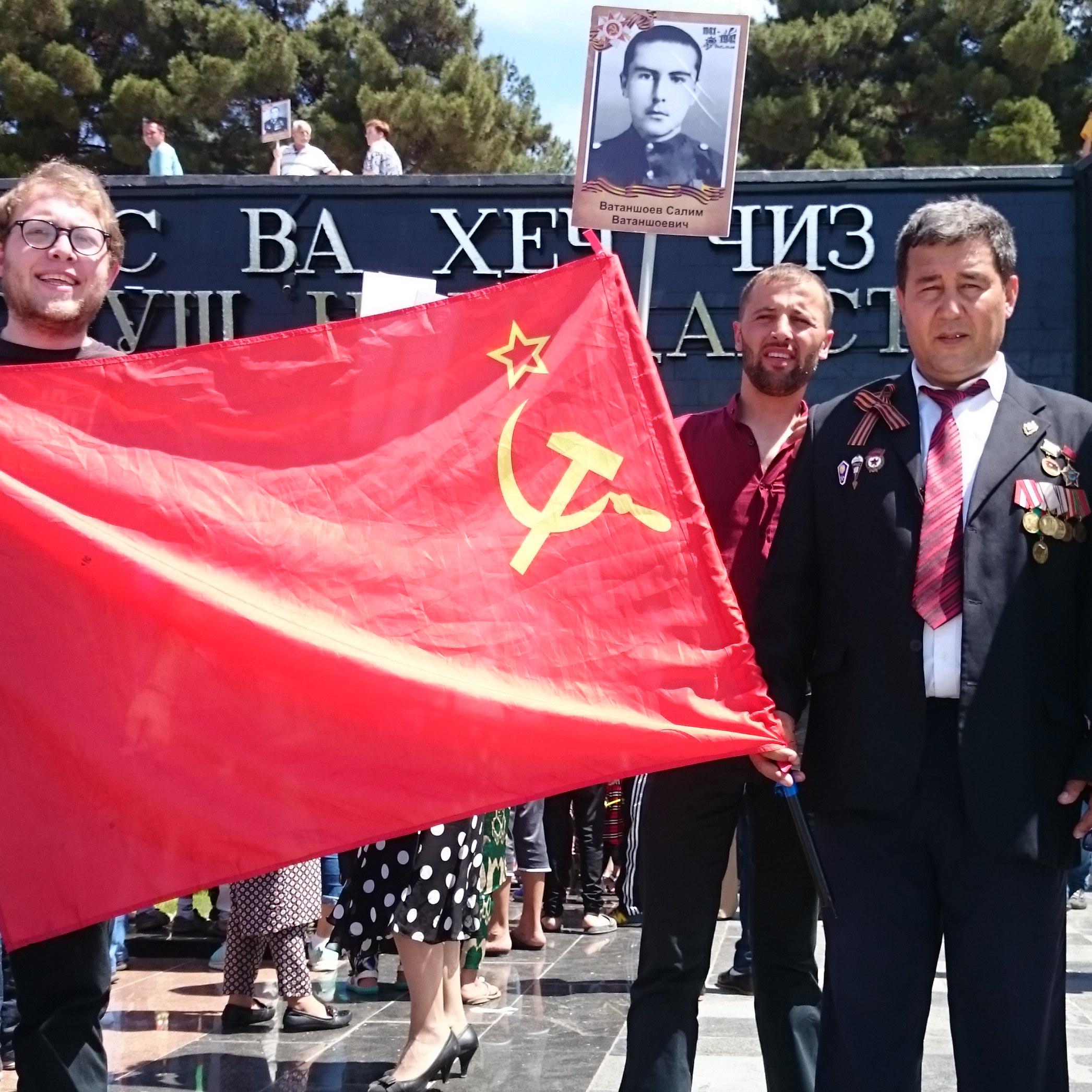 Ein Mann mit vielen Orden posiert stolz neben einer Sowjetflagge.