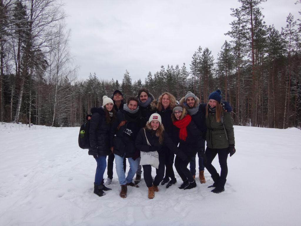 Gruppe junger Studenten auf einer Lichtung im schneebedckten Wald