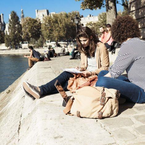 Zwei Studierende lernen am Ufer der Seine in Paris.