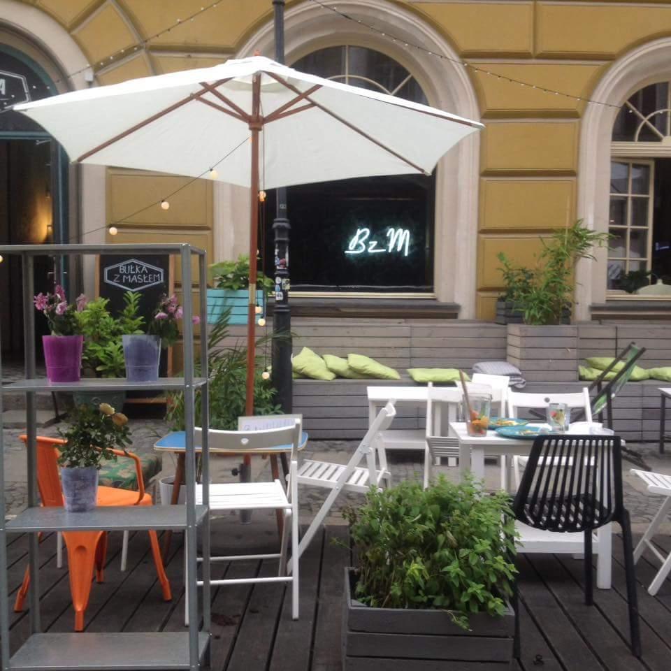 Die Terrasse eines Cafés, mit sonnenschirmen, Tischen und Stühlen und unvollendet liebevollen details und vor allem mit vielen frischen Pflanzen