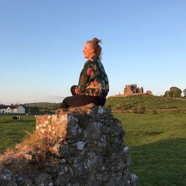 Silva sitzt auf einem Felsen in einer grünen irischen Landschaft