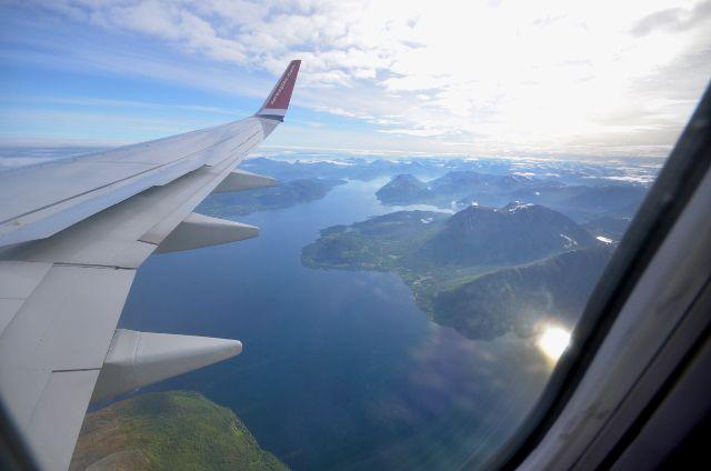 Blick aus einem Flugzeugfenster auf eine bergige Fjordlandschaft