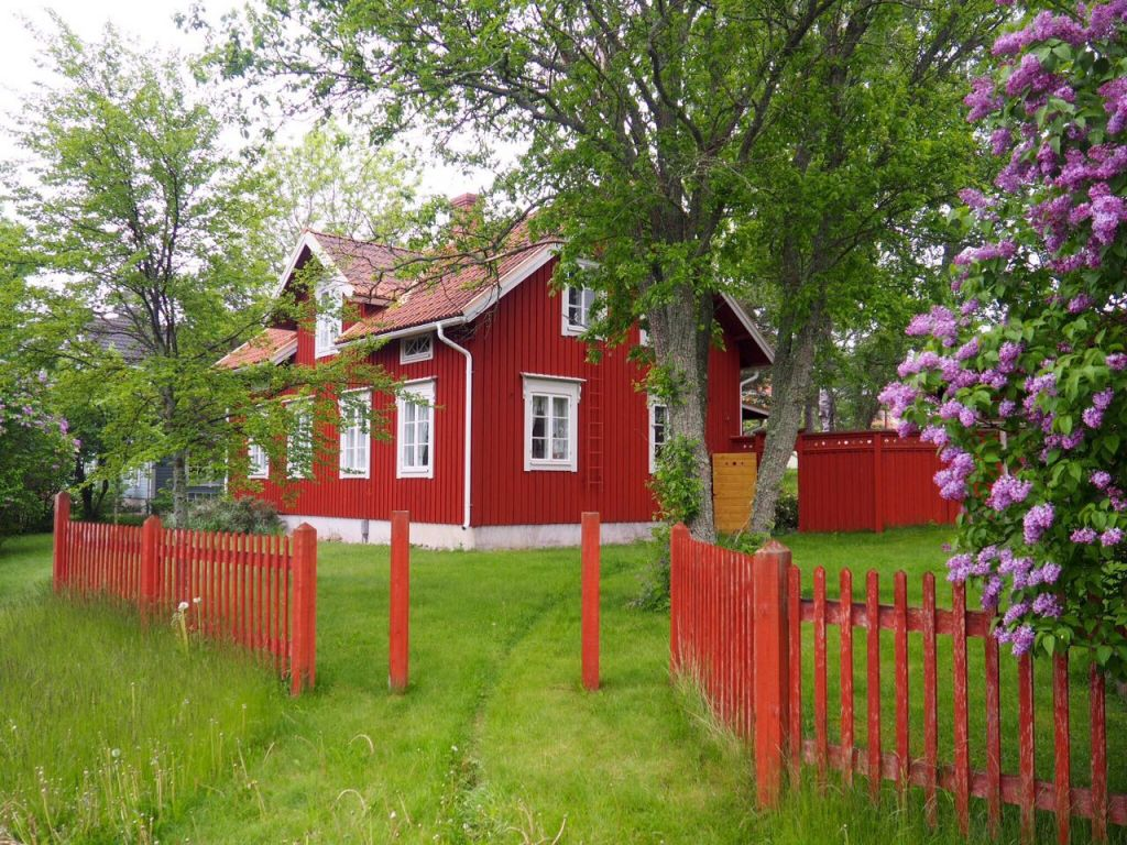rotes Holzhaus umgeben von grünen Bäumen