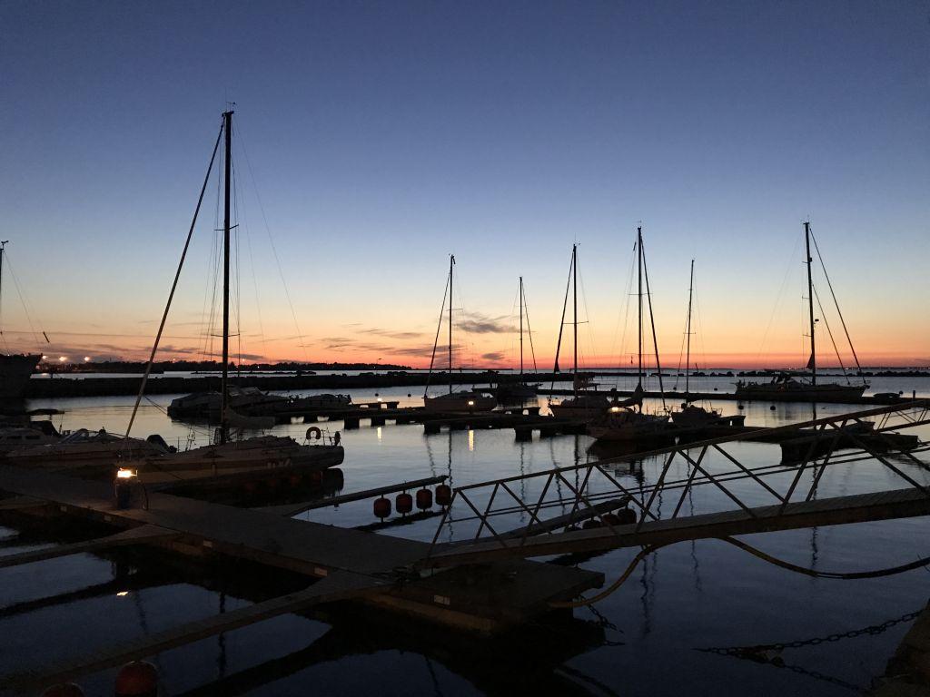 Sonnenuntergang am Wasser mit Segelbooten