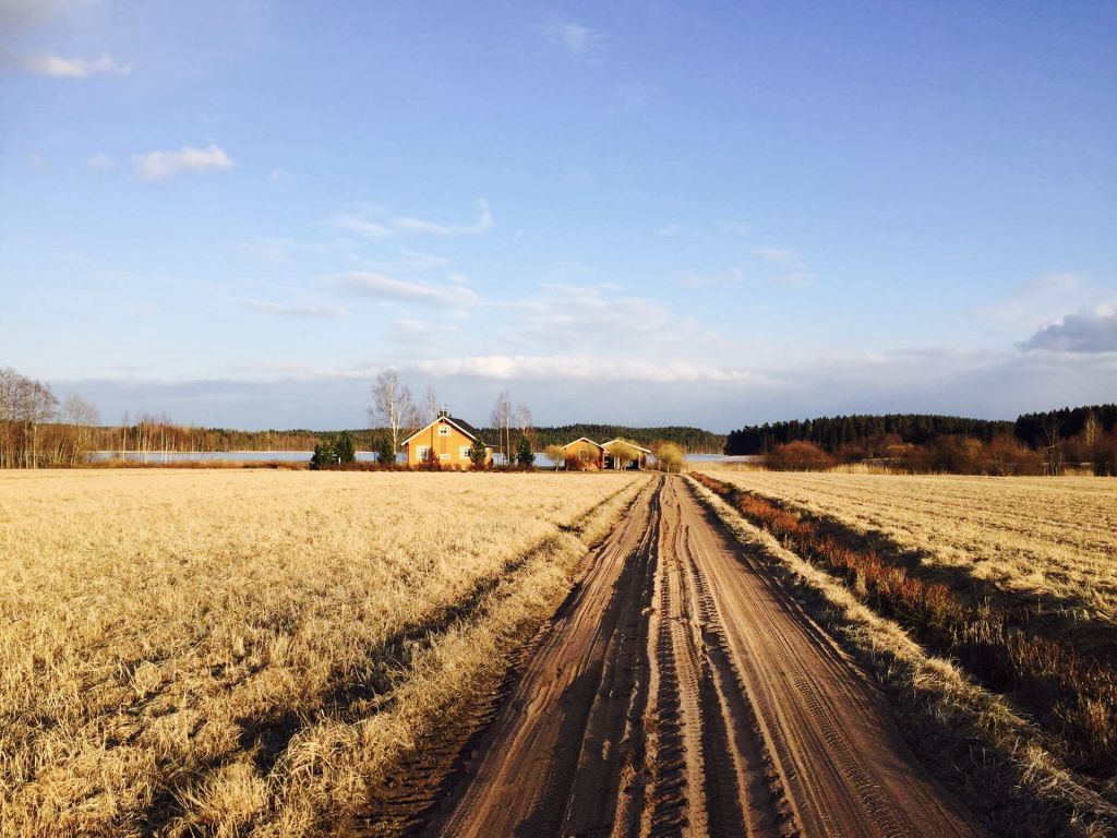 langer Feldweg mit Haus am Ende