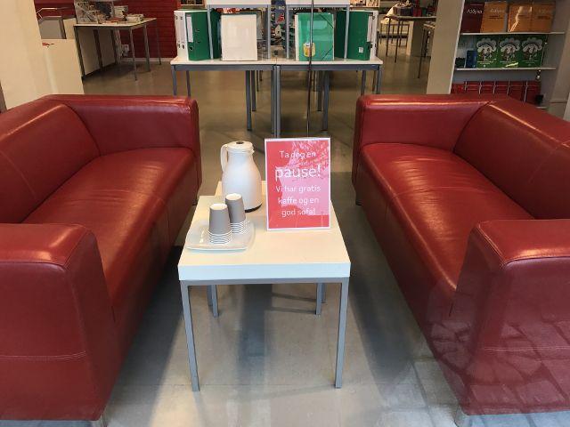 Zwei rote Sofas mit Tisch in der Mitte, darauf Gratis-Kaffee
