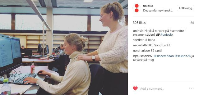 Eine Frau massiert den Nacker einer anderen Frau, die vor ihr an einem Computer arbeitet