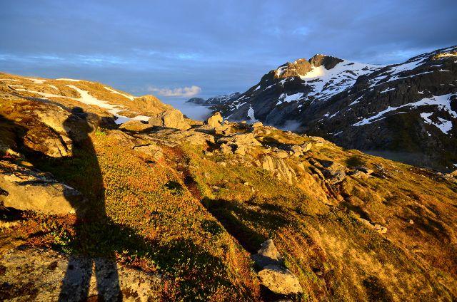 Berglandschaft mit Abendsonne, im Vordergrund langer Schatten eines fotografierenden Mannes