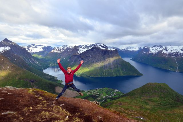 Mann springt vor Fjordpanorama in die Luft