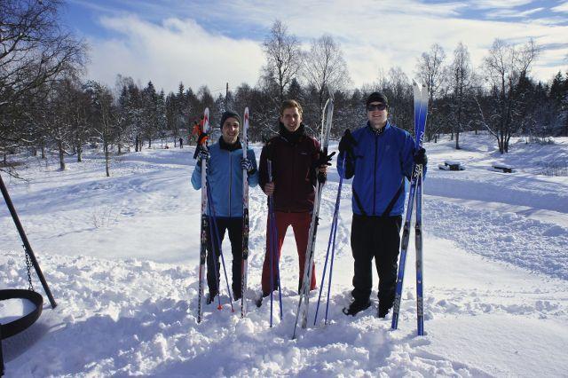 Drei Männer stehen im Schnee und halten Skier zum Langlaufen in der Hand
