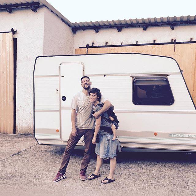 zwei Personen mit Kind vor Wohnwagen